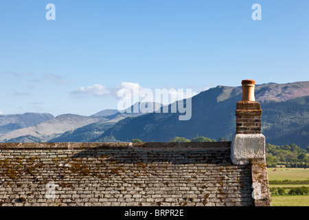 Old slate roof house roof and chimney overlooking mountains, Cumbria, England, UK - Stock Photo