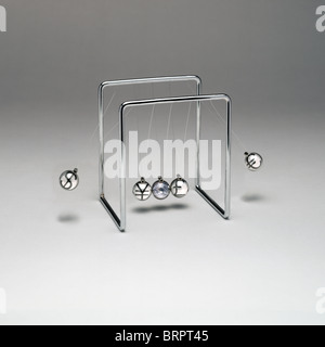 Newton's Cradle with currency symbols on gradated background - Stock Photo