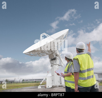 Workers with satellite dish - Stock Photo