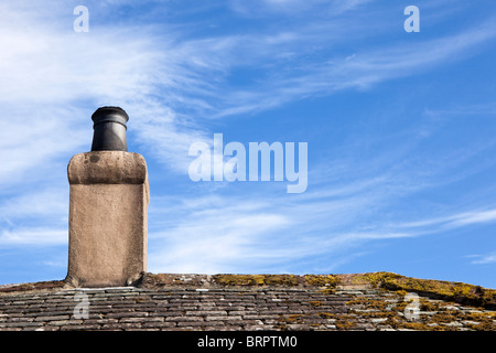 Old rendered chimney pot stack on a slate roof UK - Stock Photo