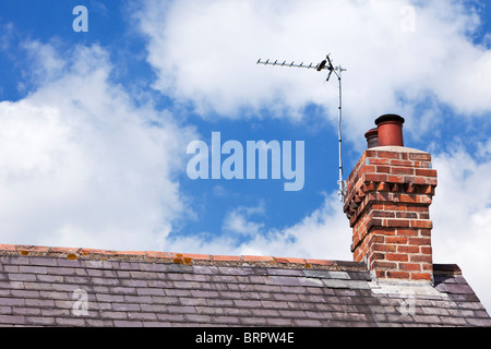 TV aerial on a house slate roof with red brick chimney stack UK - Stock Photo