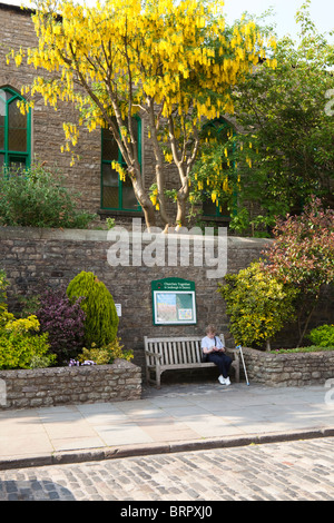 A springtime rest on a public bench in the main street in Sedbergh, Cumbria - Stock Photo