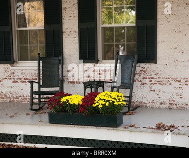 Pair of old rocking chairs on porch of old building in fall - Stock Photo