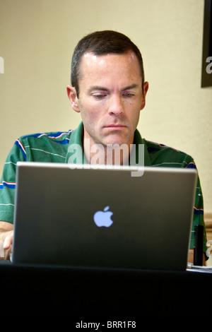 A man works on an Apple laptop, Kearney, NE, June 1, 2010. - Stock Photo