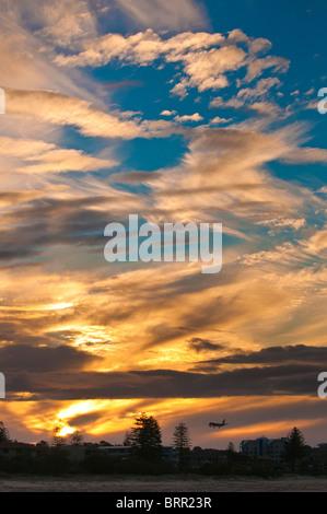 Commercial passenger jet landing under wispy clouds at sunset, Gold Coast Airport, Queensland, Australia - Stock Photo