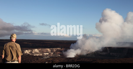 Tourist outside the Thomas A. Jagger Museum on the Big Island looks at fume cloud - Stock Photo