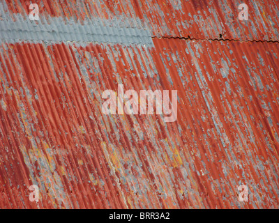 Close up of corrugated iron roof with peeling red paint - Stock Photo