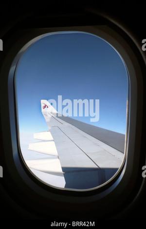 View through aeroplane window of wing - Stock Photo