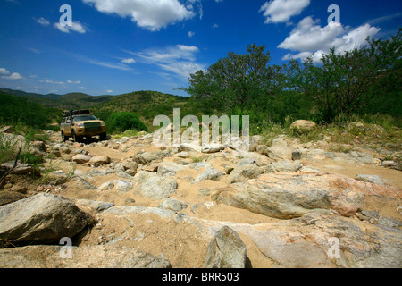 A 4x4 vehicle drives over big rocks on a bad road - Stock Photo