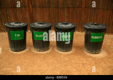 A row of recycling bins for tins, glass, food waste and unclassified rubbish - Stock Photo