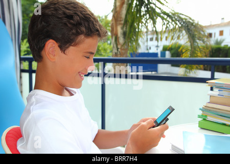 Teenager student boy sms message on mobile phone outdoor garden - Stock Photo