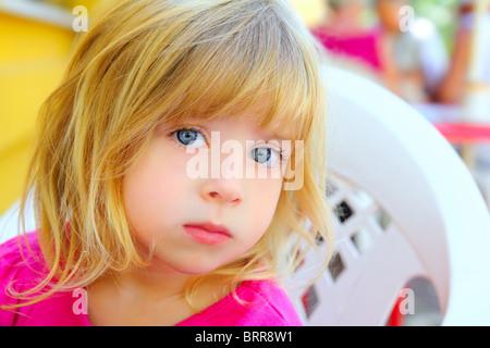 blond little girl portrait looking camera pink dress blue eyes - Stock Photo