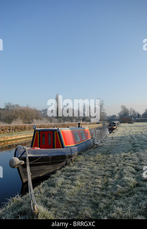 A red and blue narrowboat moored on the canal side covered in a sharp frost with a clear blue sky  on a winter morning - Stock Photo