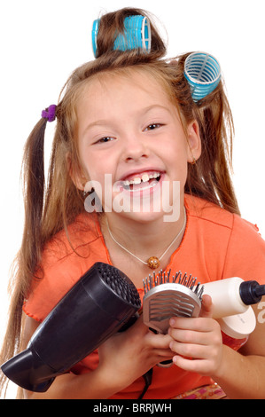 Girl with a comb in hair curlers on a white background - Stock Photo
