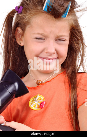 Girl with developing hair and hairdryer - Stock Photo