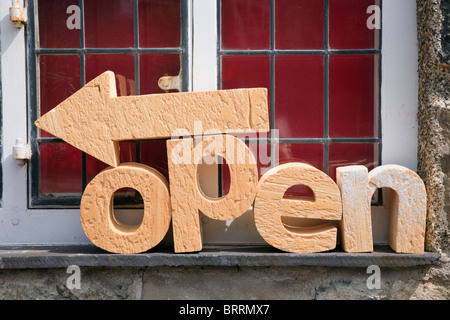 UK. Open sign with letters in carved stone by Tom Gloster in workshops for local crafts. - Stock Photo