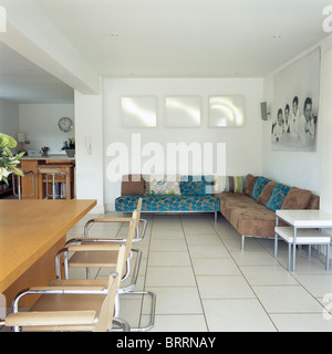 Dark turquoise+brown corner sofa and cantilevered chairs in large modern kitchen and dining room with white tiled - Stock Photo