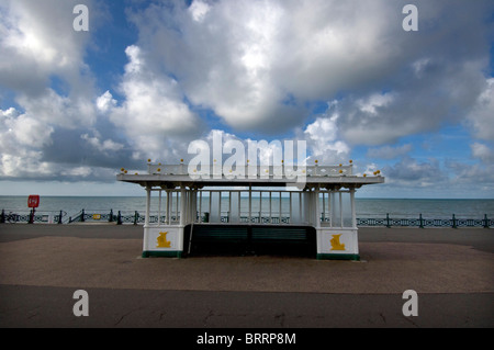 A 1860s beach shelter on the seafront at Kings Esplanade on Hove promenade with puffy cumulus clouds above. - Stock Photo