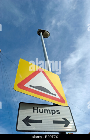 british road sign indicating speed humps on both sides of the road, with arrows pointing left and right - Stock Photo