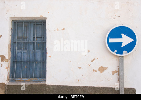 Blue keep right sign against peeling whitewashed wall and old blue window - Stock Photo