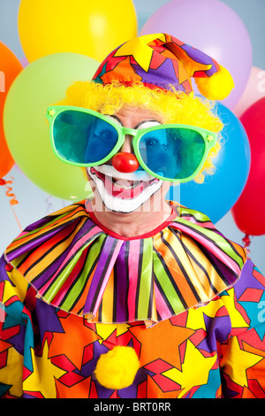 Funny birthday clown wearing over-sized novelty sunglasses.  - Stock Photo