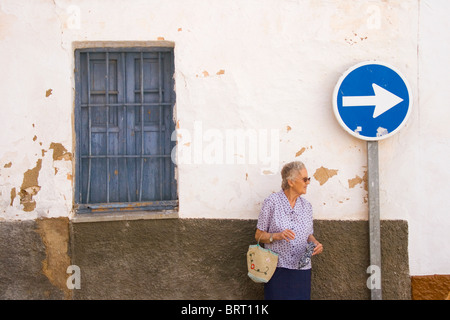 Old lady stood waiting in front of peeling whitewashed wall. - Stock Photo