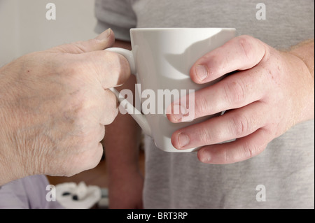 male carer (son) giving a cup of tea / coffee to a disabled elderly man - Stock Photo
