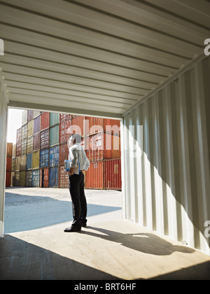 portrait of mid adult businessman standing near cargo container. Vertical shape, side view, copy space - Stock Photo