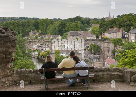 Three people sitting on a bench admiring the view over the River Nidd at Knaresborough. - Stock Photo