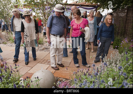 Visitors to the Tatton Park flower show take an interest in a water feature in one of the display gardens. - Stock Photo