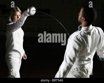 Two fencers, a young woman and a young man, in a confrontation - Stock Photo