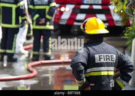 Firefighter brigade at work. Shallow depth of field. - Stock Photo