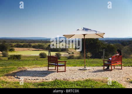 Woman looking at watering hole at River Bend Lodge, Addo Elephant Park, Eastern Cape, South Africa - Stock Photo
