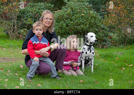 a mother, her two young children and the family dog sitting in a meadow - Stock Photo