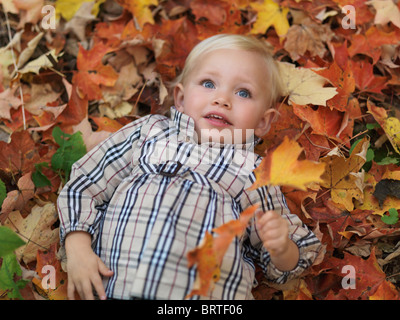 Two year old girl lying on fallen tree leaves in autumn nature - Stock Photo