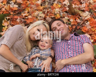 Happy smiling young parents and a two year old girl lying on colorful fallen tree leaves in autumn nature - Stock Photo