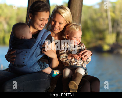 Two young mothers with their kids enjoying their time in the nature. Ontario, Canada. - Stock Photo