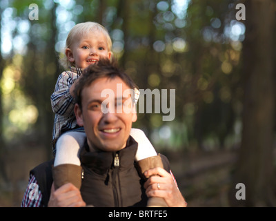 Little girl riding on her fathers shoulders in the nature. The focus is on the child. - Stock Photo