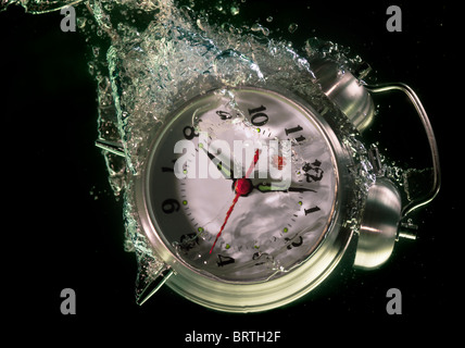 Alarm clock sinks underwater - Stock Photo