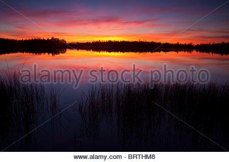 A stormy fall sunset is reflected in the waters of Cranberry Lake on the north end of Whidbey Island. - Stock Photo