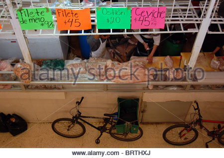 Public Mexican fish market as seen from a balcony in a marketplace showing  signs in Spanish and delivery bicycle - Stock Photo