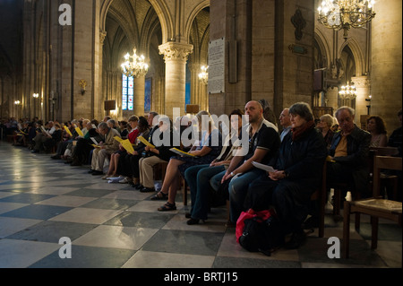 Paris, France - Crowd at Mass, inside Gothic Cathedral Catholic Church, 'Notre Dame Cathedral' religious meeting - Stock Photo