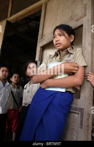 A 13-year-old 6th grade student, (front) is holding her schoolbooks at The Ban Buamlao Primary School in Ban Buamlao, - Stock Photo