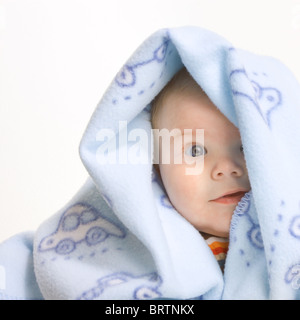 Expressive cute little boy covered by soft blue blanket isolated on white background. - Stock Photo