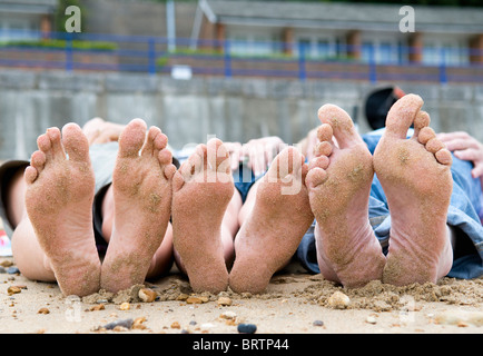 Families sandy feet on beach - Stock Photo