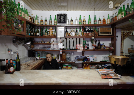 Old woman behind the counter of a traditional small bar in Alpedrinha, Portugal - Stock Photo
