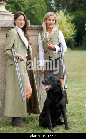 Two very attractive girls dressed for a day in the country, holding shotguns, with a  black Labrador waiting - Stock Photo