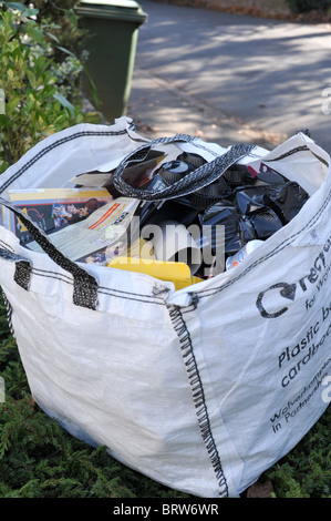 Householder's white recycling bag filled with plastic and cardboard sitting on the pavement waiting for the kerbside - Stock Photo