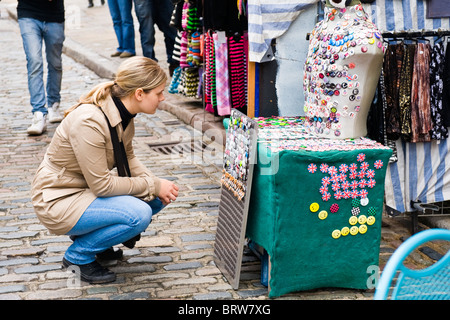Camden Town Market Lock , pretty young blond girl in leather jacket & jeans crouches by display of selecting of - Stock Photo