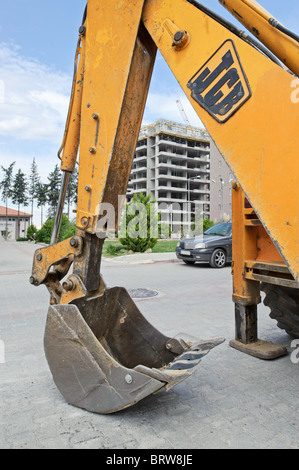 The claw of a yellow JCB digger rests on the road in front of a apartment development site. - Stock Photo